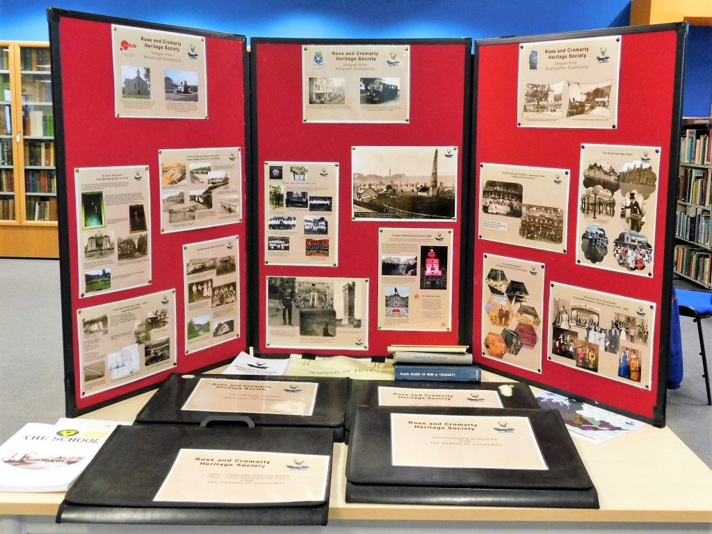 Exhibition screens with old photos and books of photos in front of them