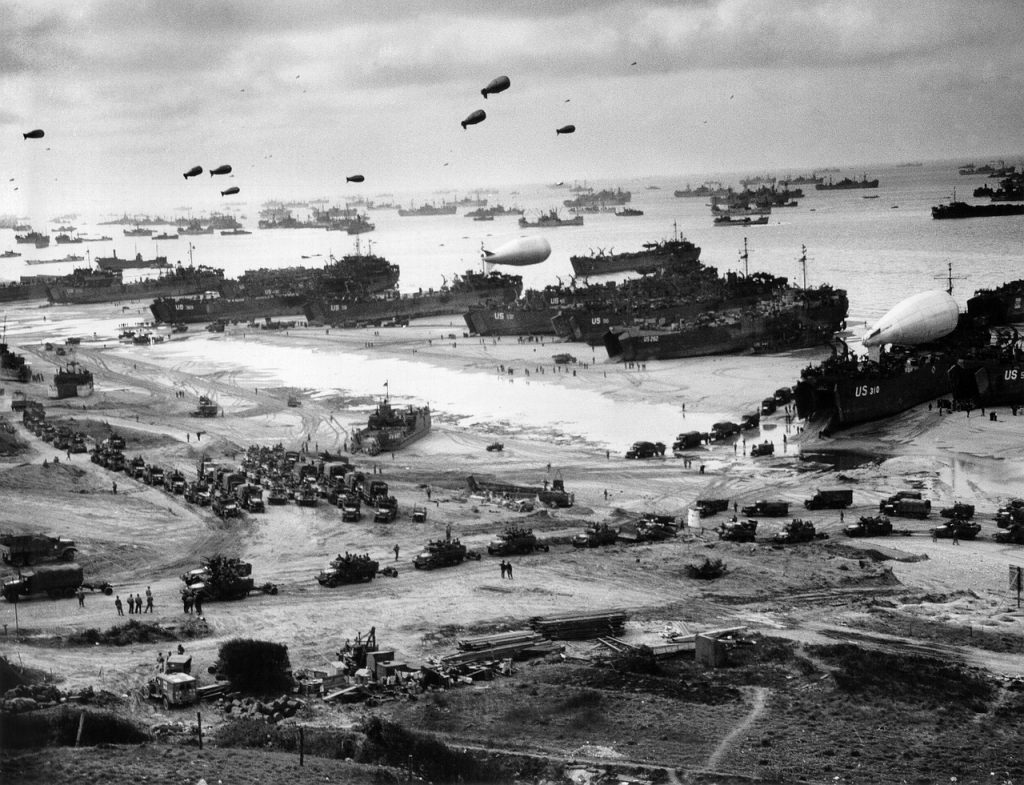 Old World War 2 beach landing photos with vehicles disembarking from ships and barrage balloons in the sky