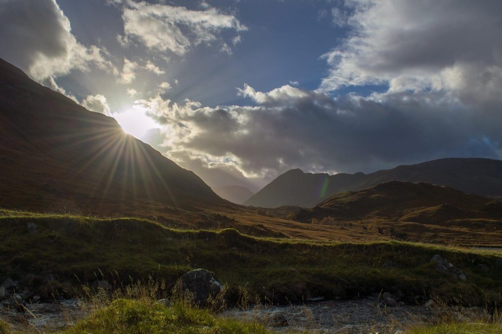Photograph of the sun emerging from behind a hill in strath Conon