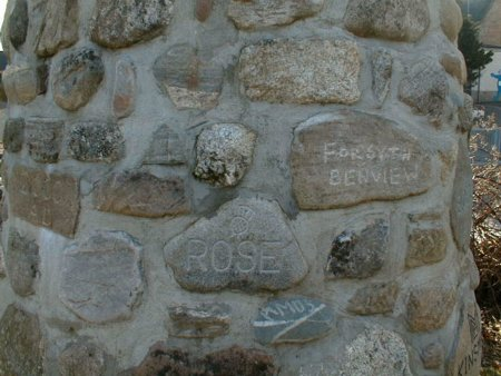 A close-up showing some of the villagers' names inscribed on the stones of the cairn.