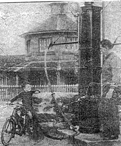 Donald Menzies, 4 year old son of Frank, getting a fill of petrol for the miniature motor cycle