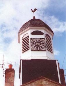 Octagonal wooden cupola with a pedimented clock face on its south front